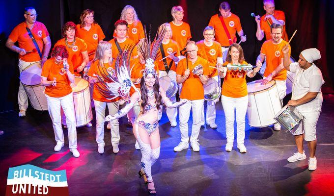 Ein Orchester in orangenen Shirts und weißen Hosen spielt Musik. Vor ihnen tanzt eine Sambatänzerin im Kostüm.