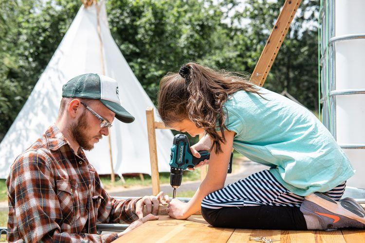 Ein junger Mann und ein Mädchen bauen etwas aus Holz. Das Mädchen sitzt auf einer Anhöhe und schraubt mit einem Akkuschrauber Holzlatten zusammen. Im Hintergrund steht ein großes weißes Tipi.