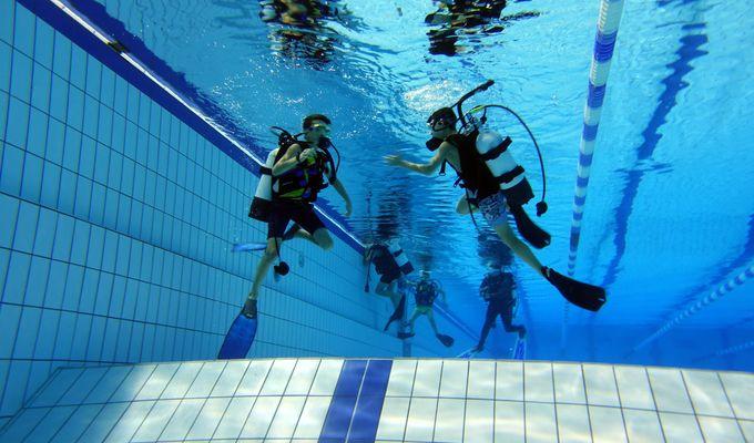 Zwei Jugendliche sind im Vordergrund mit Tauchermontur (Sauerstoffmaske & -flasche, Flossen, Brille) unter Wasser in einem Schwimmbecken zu sehen. Im Hintergrund sind noch weitere Jugendliche mit Tauchermontur zu erkennen.