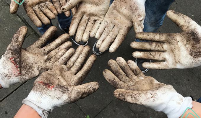 Vier Paar Hände in Gartenhandschuhen gehen in der Bildmitte zusammen. DIe weißen Handschuhe sind erdig und schmutzig. Darüber steht: gemeinsam stark