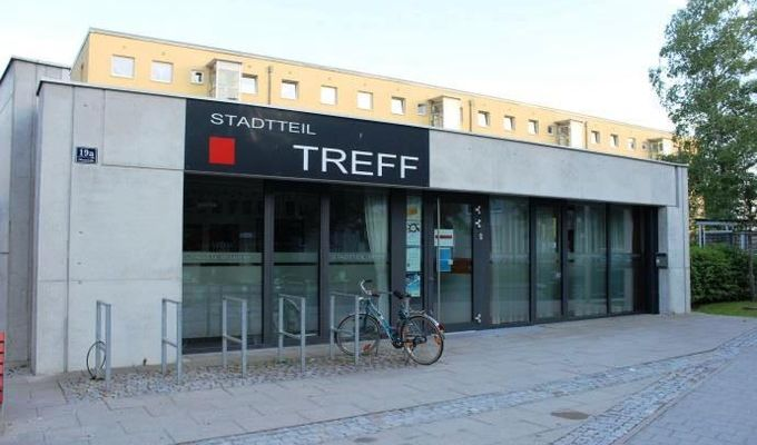 An einem grauen niedrigen Gebäude ist ein schwarzes Schild mit der Aufschrift: Stadtteil Treff, befestigt.
