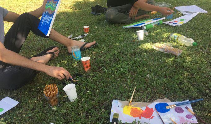 Zwei Menschen sitzen im Schneidersitz auf einem Rasen im Schatten und malen. Malutensilien, Snacks und Getränke liegen verstreut. Beide Schultern und Köpfe sind außerhalb des Bildschirmrandes, so kann man nicht genauer erkennen, wer malt.