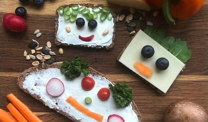 Auf einem Holzbrett liegen drei belegte Brotscheiben, sowie weiteres Obst und Gemüse. Die Brotscheiben haben Gesichter aus Obst.