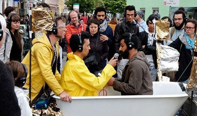 Eine Gruppe von Menschen steht um eine dekorierte Badewanne, in der zwei Personen sitzen. Die eine Person hält ein Mikrofon zu der anderen sprechenden Person. Alle Beteiligten tragen Kopfhörer.