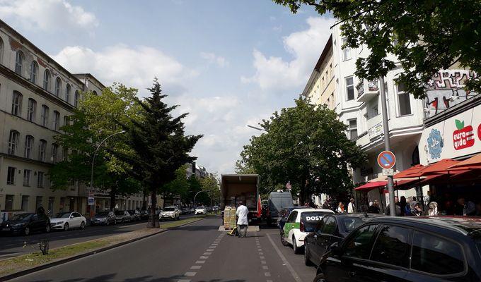 Blick in eine doppelspurige Straße mit parkenden Autos. Die Sonne scheint und die Bäume am Straßenrand sind grün.