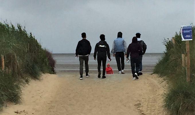 Fünf Männer sind von hinten zu sehen, wie sie einen breiten Sandweg entlang auf das Meer zugehen. Rechts und links vom Weg sind Dünen mit Strandhafer-Bewuchs. Der Himmel ist grau.