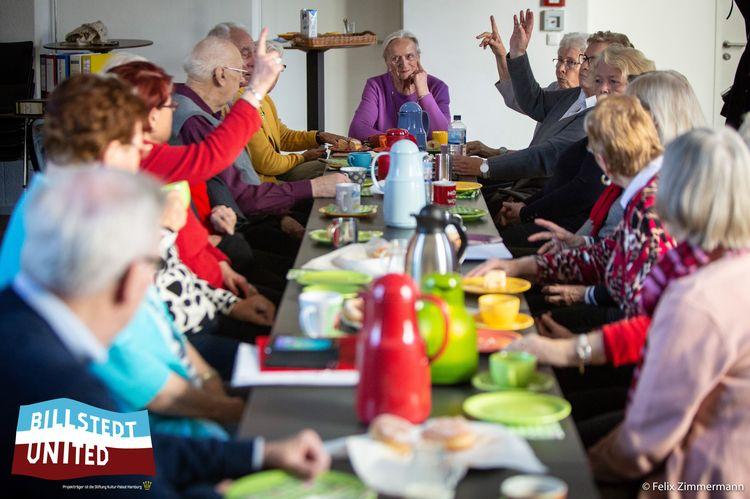 Eine Gruppe von Senioren sitzen gemeinsam beim Kaffe trinken. Einige von ihnen melden sich.