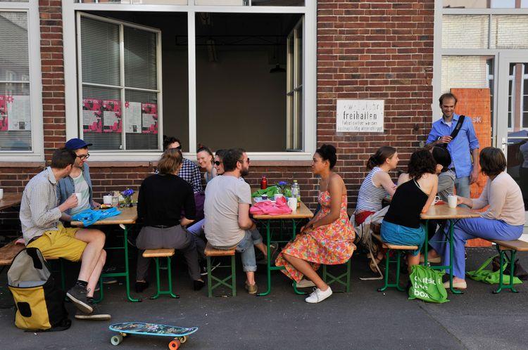 Eine große Gruppe junger Personen sitzen auf Bierzeltgarnituren vor einem Gebäude und unterhalten sich.