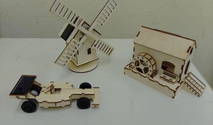 Modelle von einem Rennauto, einer Windmühle und einer Wassermühle. Sie bestehen aus dünnem Holz, wahrscheinlich Pressspahn. Auf dem Spoiler des Rennautos und dem Dach der Windmühle befinden sich kleine Solarzellen. Sie stehen auf einem weißen Tisch vor einer weiß-beigen Wand.