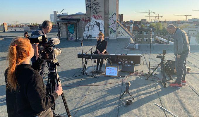 Eine Künstlerin sitzt am Keyboard auf dem Dach des Quartiersmanagement. Drum herum sieht man das Kamerateam, die Sonne steht tief und gibt ein schönes Ambiente