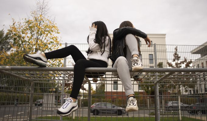 Zwei Mädchen mit langen Haaren sitzen, zur Seite wegguckend und Füße angewinkelt, auf einem Metalltor nebeneinander.