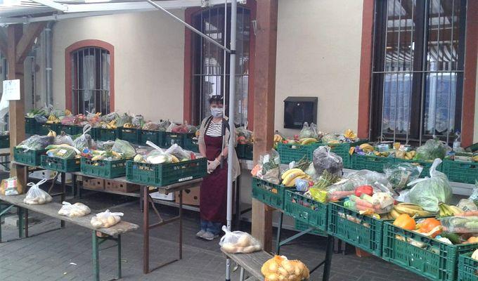 Eine Frau steht zwischen Vergabeständen auf den Kisten vollgepackt mit Lebensmitteln stehen.