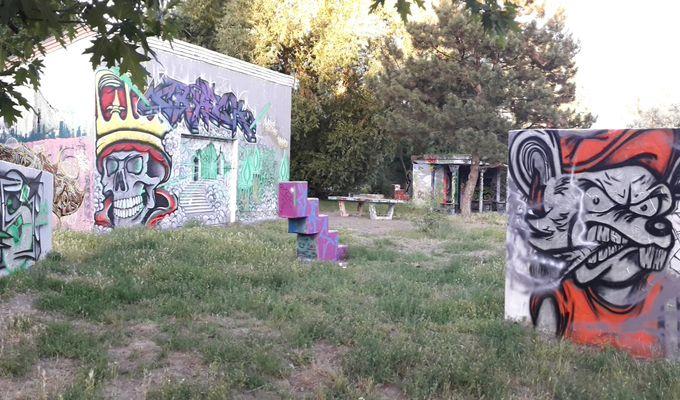 Auf einem verwilderten Platz sind Gebäude mit bunten Graffitibildern. Ein Graffiti rechts, zeigt eine zornige Maus mit roter Schirmmütze und Zigarette.