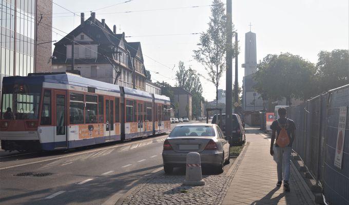 Eine Straßenbahn fährt links die Straße hoch. Rechts parken zwei Autos und eine Person geht den Fußweg entlang. Die Sonne scheint.