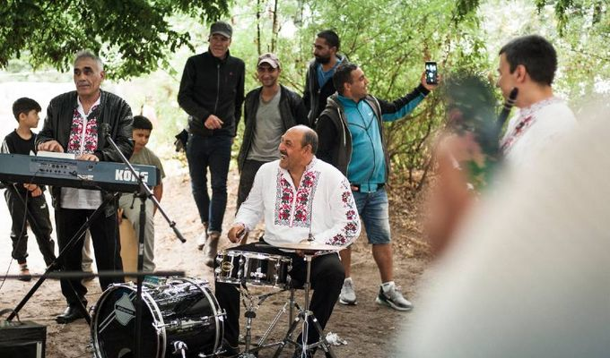 Zwei Männer spielen Keyboard und Schlagzeug. Sie sind im Freien unter einem Baum Der Boden ist blanke Erde. Um sie herum stehen Menschen und hören zu