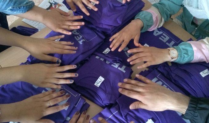 Sechs Jugendliche halten ihre Hände, mit Handflächen nach unten, im Kreis. Unterhalb der Hände liegen gefaltete Stapel mit lila Oberteilen.