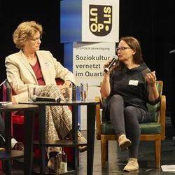 Zwei Frauen sitzen auf Stühlen auf einer Bühne für eine Podiumsdiskussion. Die rechte spricht in ein Mikrofon während die Linke zuhört. Im Hintergrund sieht man auf einem Banner das Utopolis-Logo