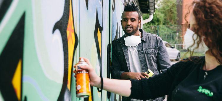 Ein Mann mit Spraydose in der Hand steht an angelehnt an eine Wand, an die eine Frau etwas sprüht.