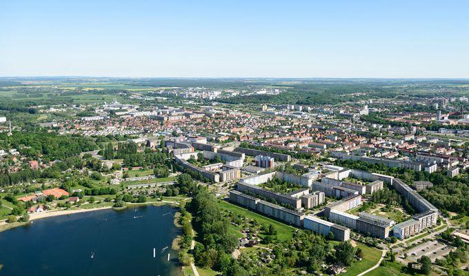 Eine sommerliche Luftbildaufnahme mit Blick zum Horizont: eine Stadt mit viel Begrünung und ein See.