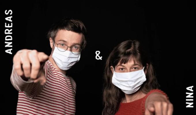 Zwei Menschen mit Hygienemasken stehen vor einem schwarzen Hintergrund und zeigen mit ihren Zeigefingern in die Kamera. Links steht Andreas, rechts Nina. Die Namen sind mit weiß auf das Bild geschrieben. Zwischen ihnen ist ein &-Zeichen