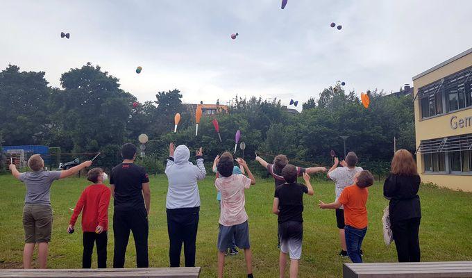 8 Kinder unterschiedlichen Alters stehen auf Rasen in einer Reihe, sie sind von hinten aufgenommen. In der Luft sind bunte Bälle, Keulen und Diabolos, mit denen sie gerade jonglieren. Rechts am Bildrand ist gerade so das gelbe Schulgebäude zu sehen