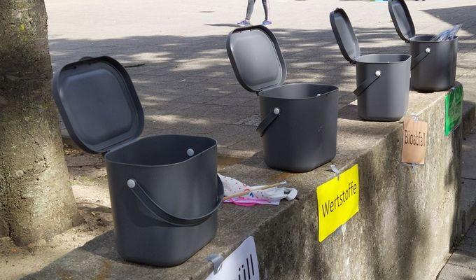 Vier graue Mülleimer stehen auf einer Mauer in einem öffentlichen Raum. Die Deckel der Mülleimer sind offen. An der Mauer sind Schilder unter den Eimern befestigt wie z.B Restmüll, Wertstoffe, Bioabfall etc.