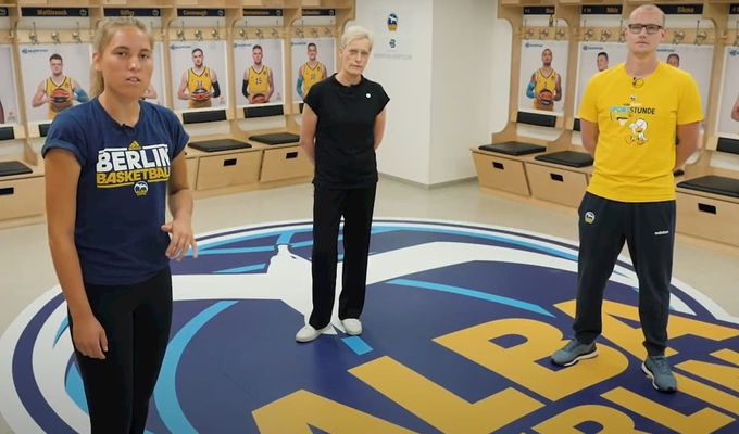 Die beiden Jugendtrainer von ALBA BERLIN und Staatsekretärin Anne Kathrin Bohle stellen das neue Programm vor. Sie sind in der Mannschaftsumkleide von ALBA BERLIN und tragen Sportkleidung.