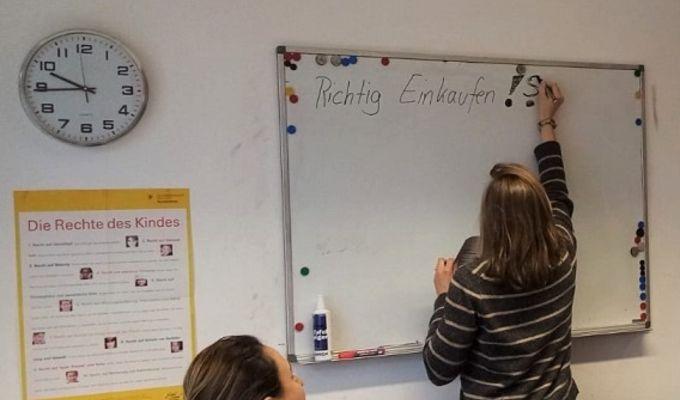 Die beiden Seminarleiterinnen der Veranstaltung. Eine sitzt am Lehrerpult, eine weitere schreibt gerade die Überschrit an das Whiteboard