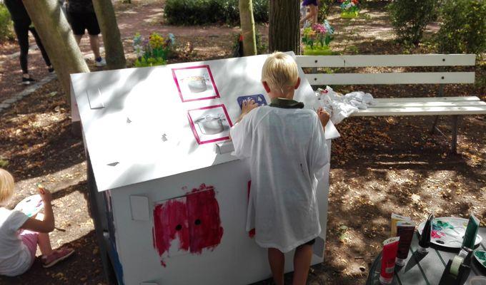 Ein Kind bemalt mit Farbe ein weißes Papphaus.