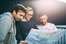 3 junge Menschen schauen auf eine Karte