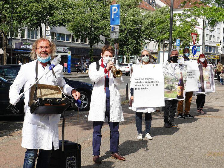 Sechs Personen in weißen Kitteln und Mundschutz stehen mit Schildern am Körper auf einer Straße. Zwei von ihnen spielen Instrumente.