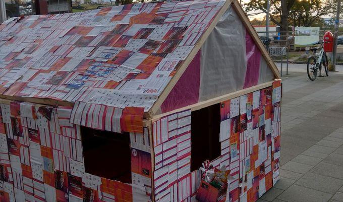 Ein kleines Haus mit Dach und Fenstern steht auf einem Bürgersteig. Es hat ein Holzgerüst und ist über und über mit Flyern beklebt. Es ist etwa so groß, dass ein Kind gut hereinpasst und Erwachsene sich sehr bücken müssen