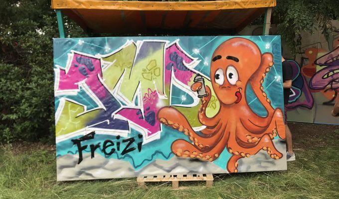 Eine große Leinwand mit Graffitibild steht angelehnt im Grünen. Neben einem bunten Schriftzug ist ein orangener Oktopus mit Spraydose.